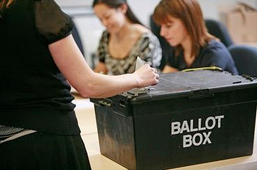 A black sealed ballot box being carried towards two female counters