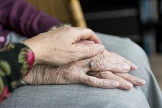 Two clasped hands, belonging to an elderly couple.