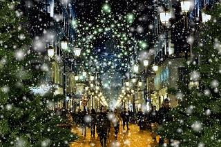 A street scene with Christmas lights, snow and people shopping