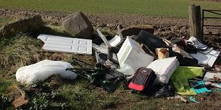 A stick image of fly tipped household waste in the countryside